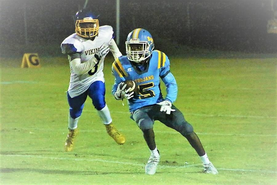 Trojan player runs past opponents