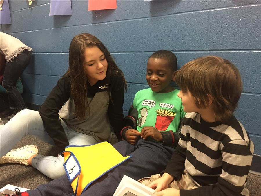 Sammy reading with elementary kids